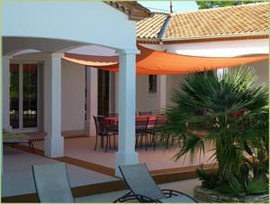 Une jolie villa avec une terrasse couverte